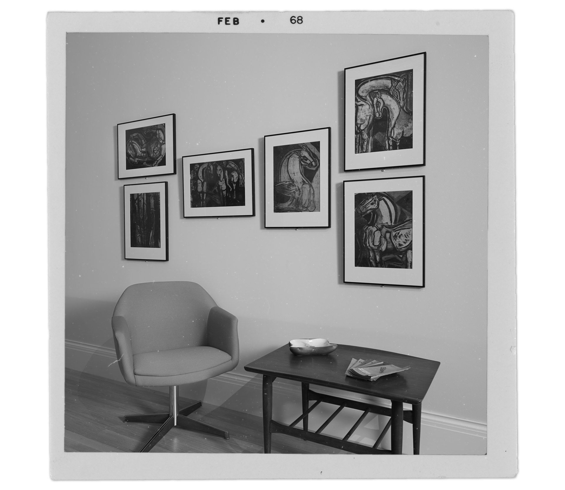 """Old"" photograph of six Delia del Carril prints hanging on a wall above a midcentury chair and table"