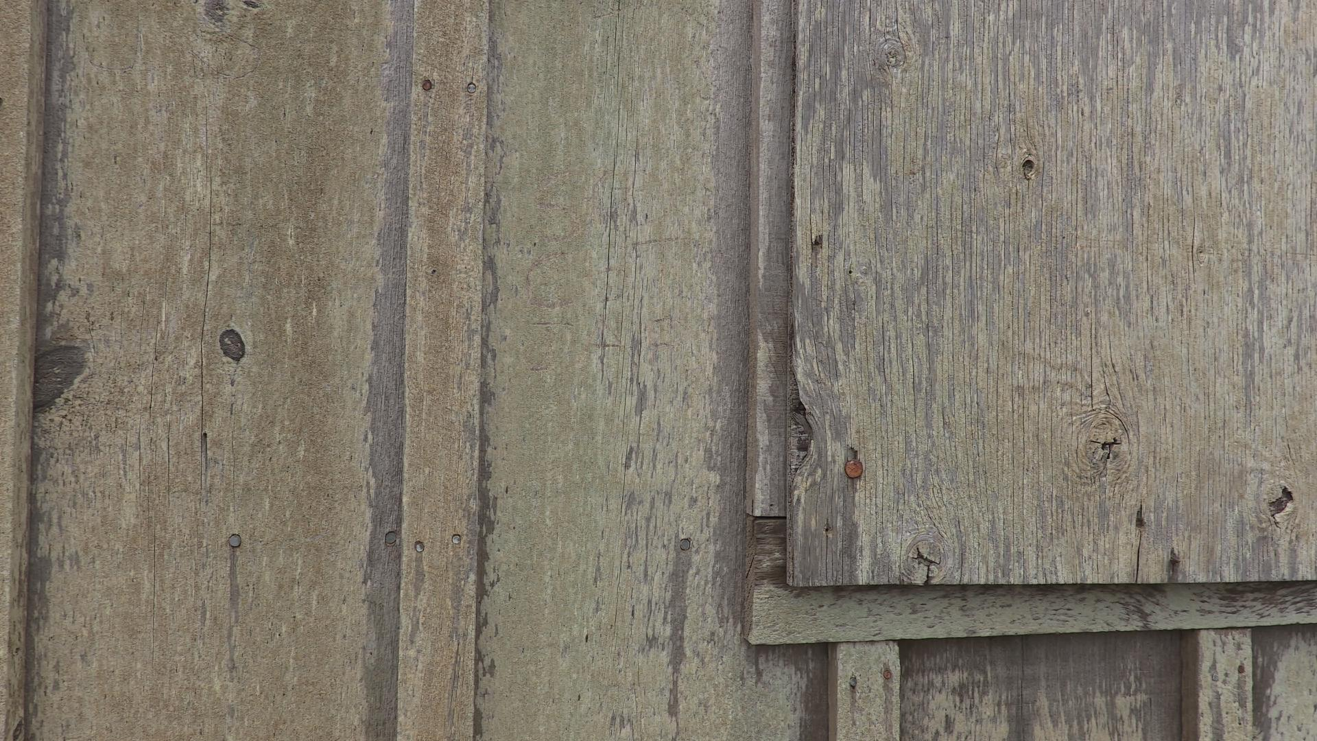 Wooden slats are shown close-up in a detail shot with weathered and rusty nails and fastners.