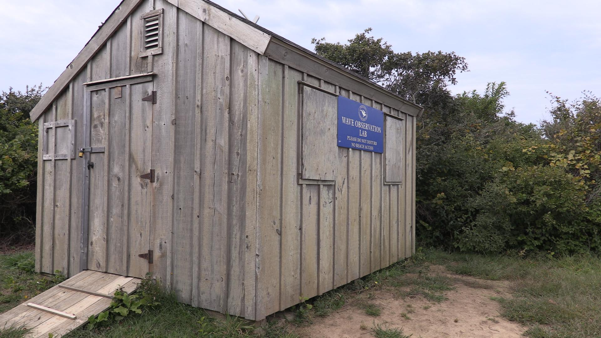 A wooden shed with a blue sign saying Cape Cod Wave Laboratory on a dirt cliff.