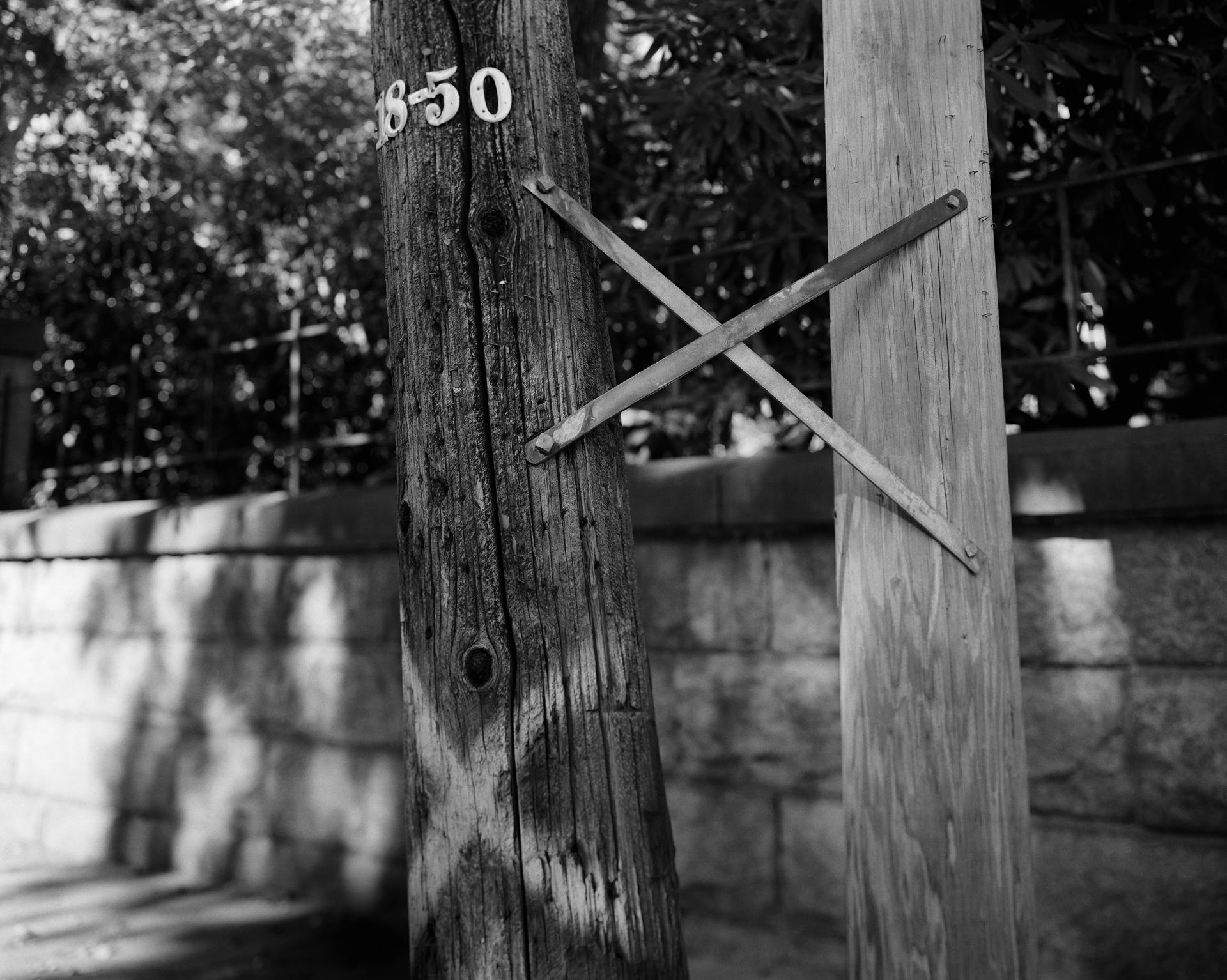 A black and white photograph of two electrical poles bound together with a metal x; one with a painted white x on the lower portion.