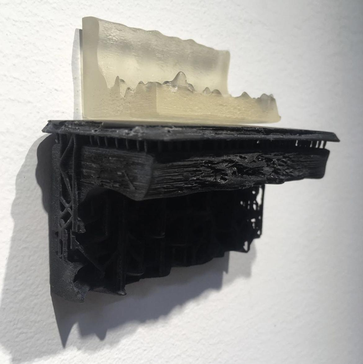 A clear representation of 3D printed waves rests on a black 3D printed mantle.