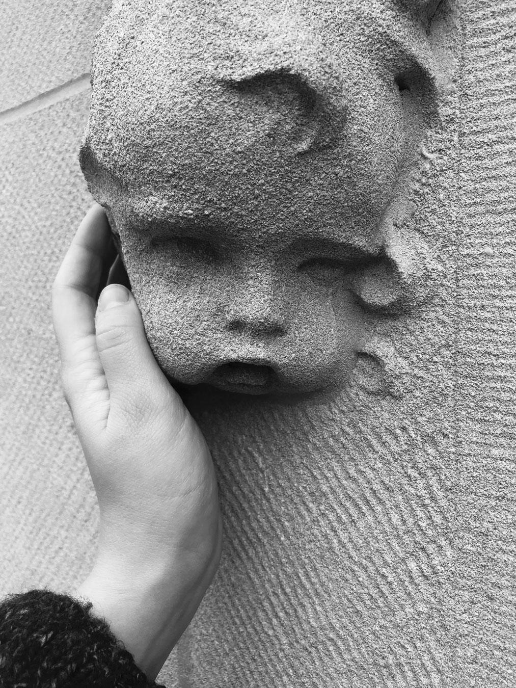 A black and white photograph of a white person's hand reaching out to touch a cherubic face made of stone.