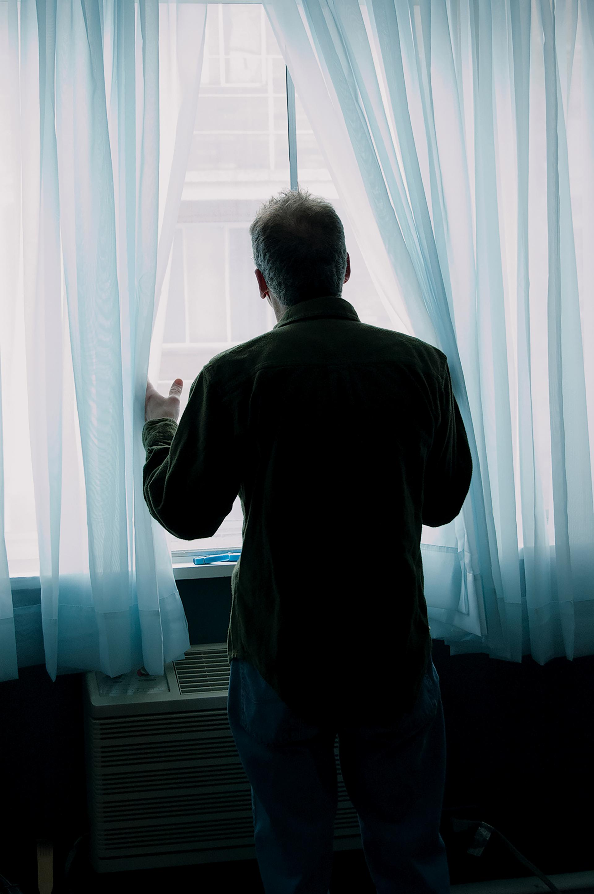 A color photograph of a person looking through translucent blue curtains, seen from behind.