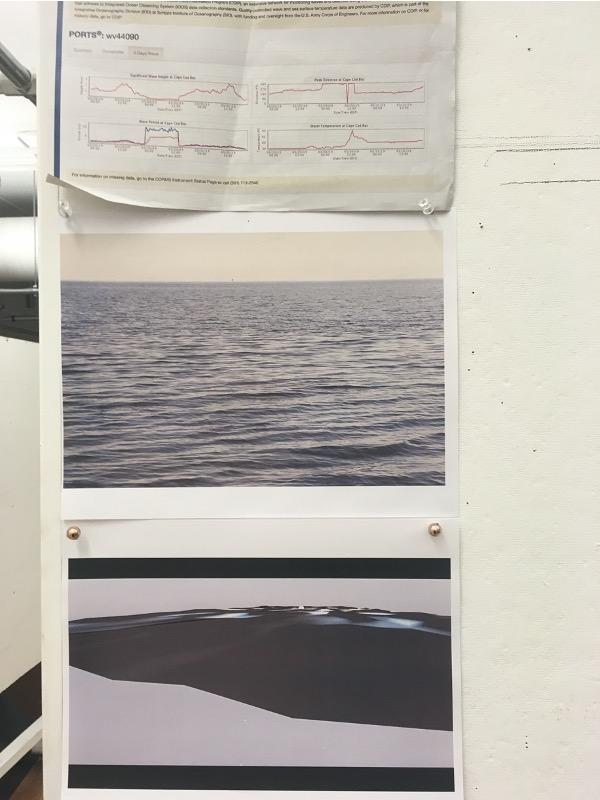 A scientific chart and pictures of waves are pinned to a wall.