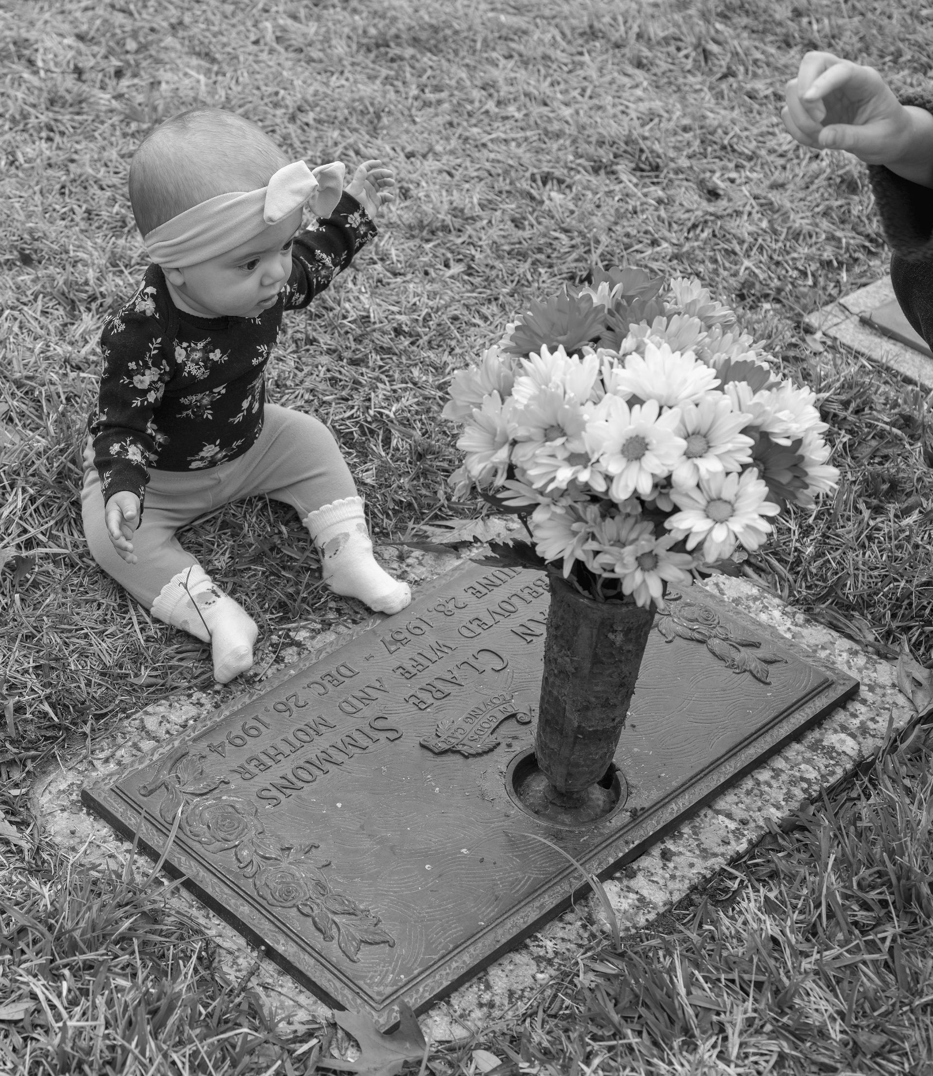 A black and white photograph of a white 6-month-old baby wearing a floral top and a bow, sitting behind a metal headstone. The headstone has a vase on top with multicolored gerbera daisies in it. A white hand is coming into the frame on the right hand side, only visible up to the wrist.
