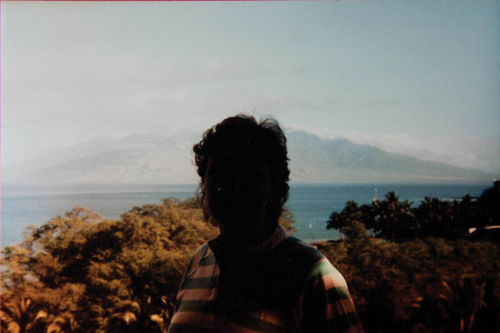 A color photograph in which a landscape can be seen behind a severely underexposed and backlit person.