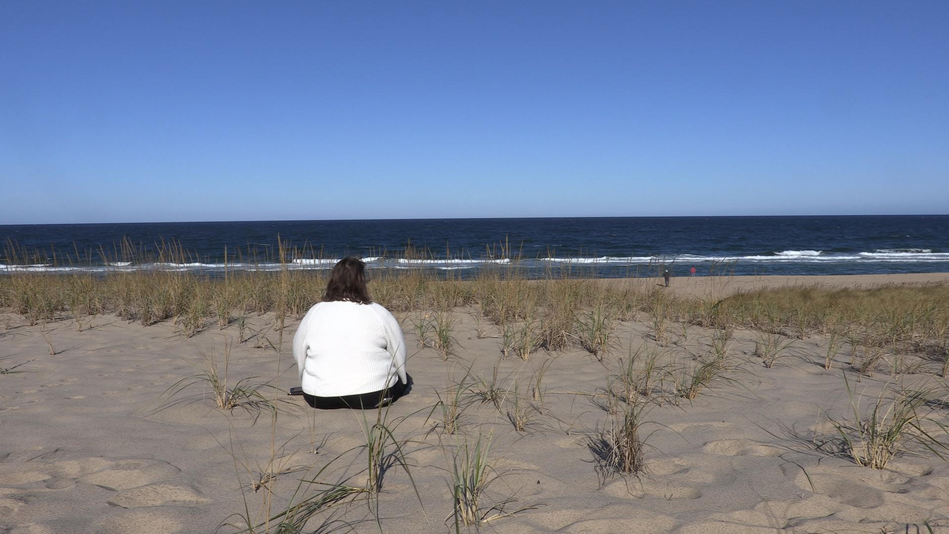 A middle aged woman sitting on a sandy beach with her back to the camera on a sunny day. She appears to be looking at the ocean in front of her.