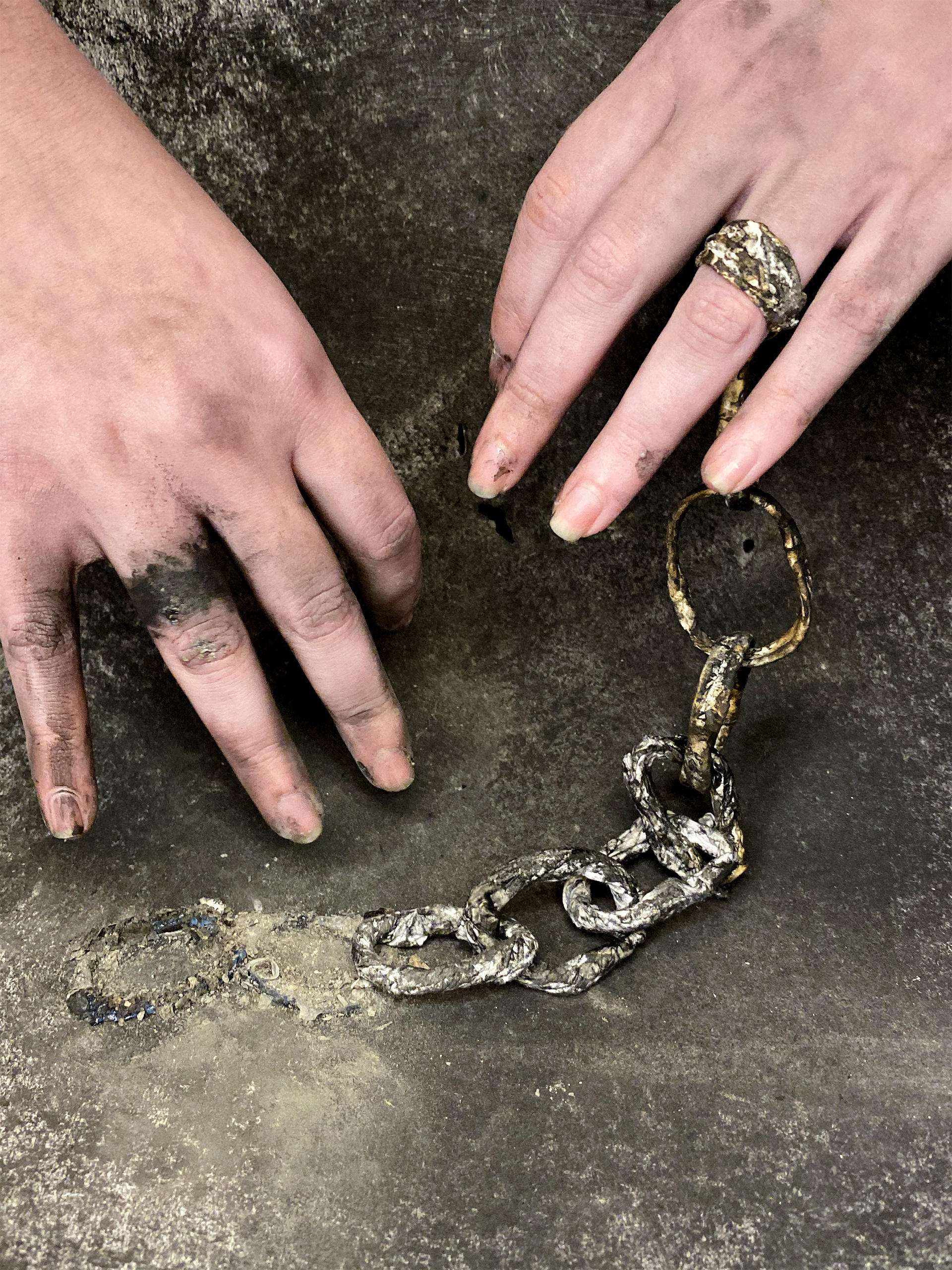 Hands with a chain and charcoal