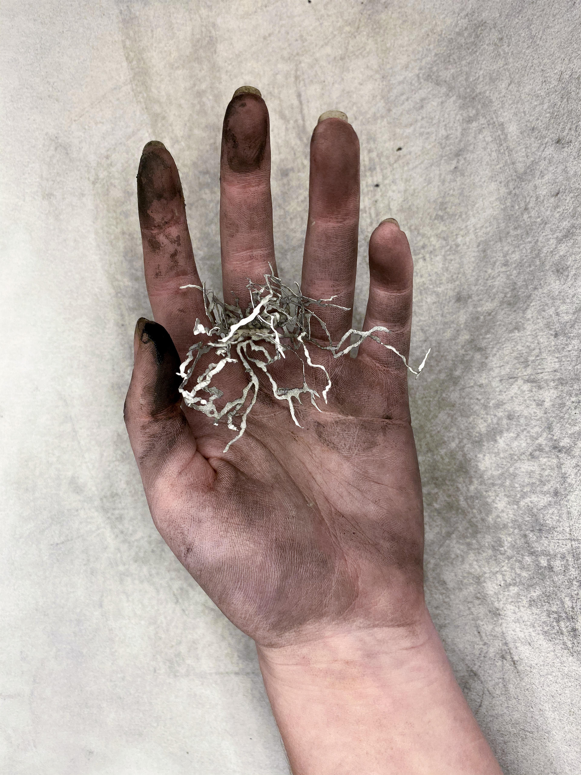 Hand covered in ash holding a small paper sculpture