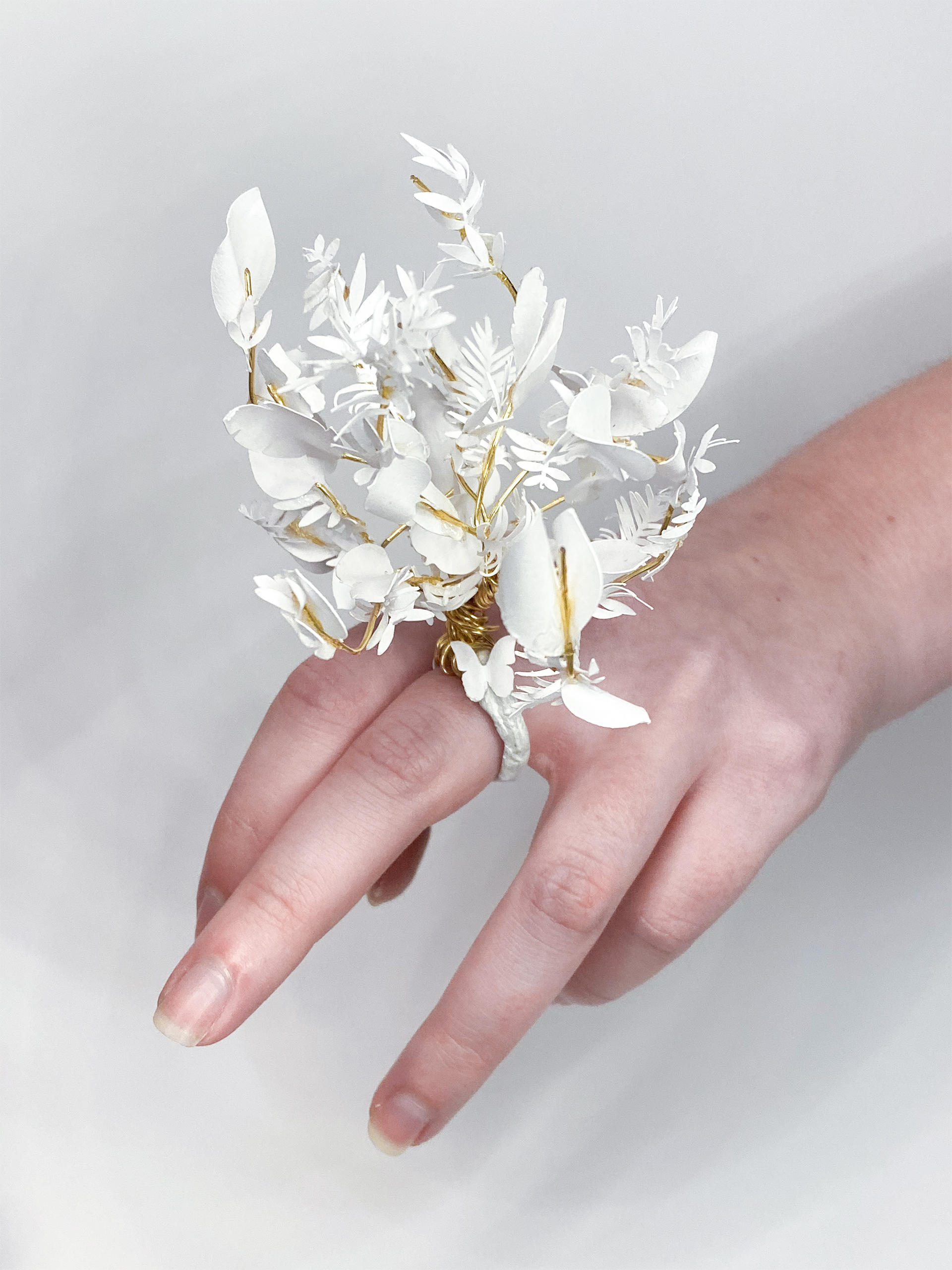 Hand with a sculptural floral ring made of paper and wire