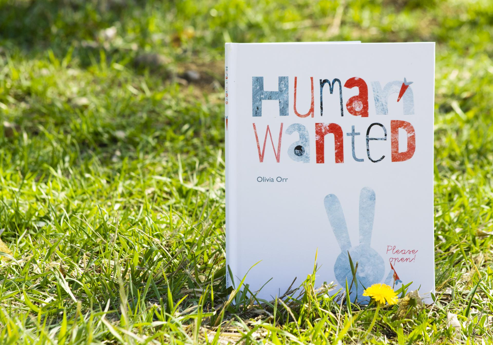 "A book titled ""Human Wanted"" displayed on grass"