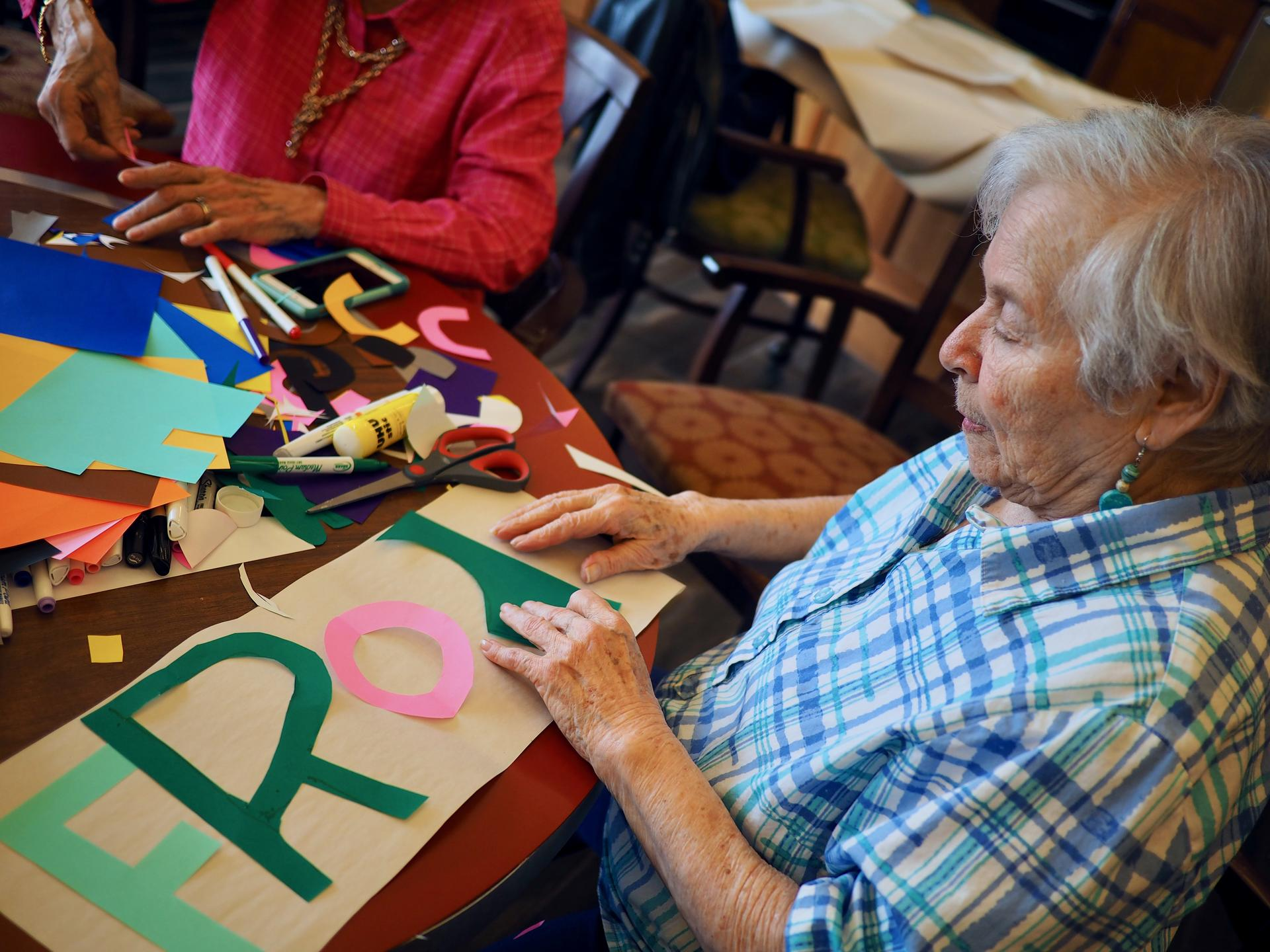 Image of an older female participant, sitting at a table and arranging brightly colored, cutout letters on a poster.