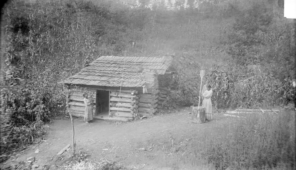 Photograph of Cherokee Medicine Man, Ayunini Swimmer, and his Log Cabin taken by James Mooney (1888).