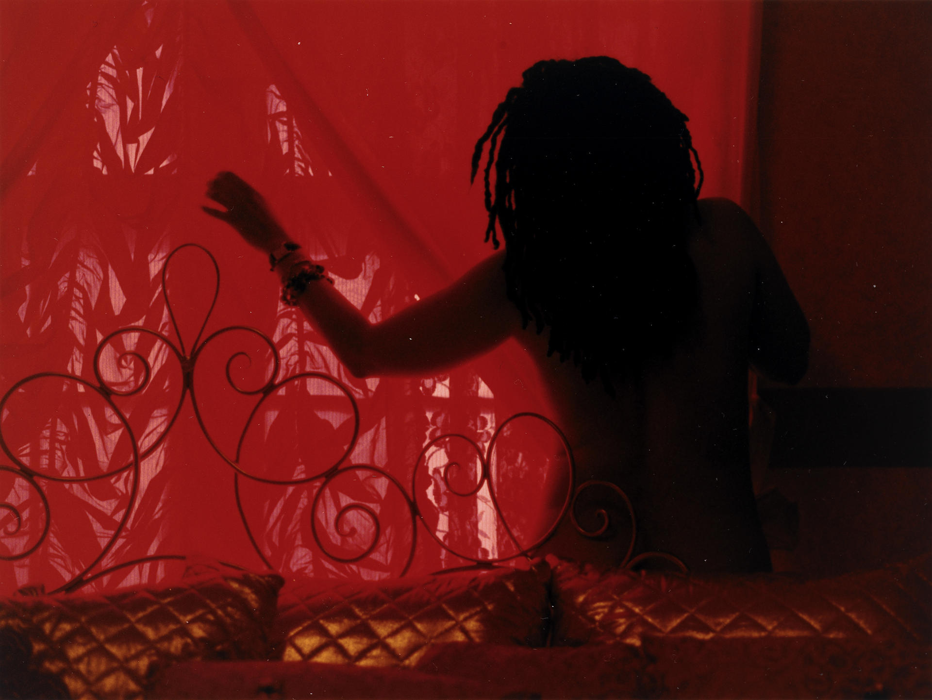 Photograph of a person with outstretched arm sillhouetted against a red window