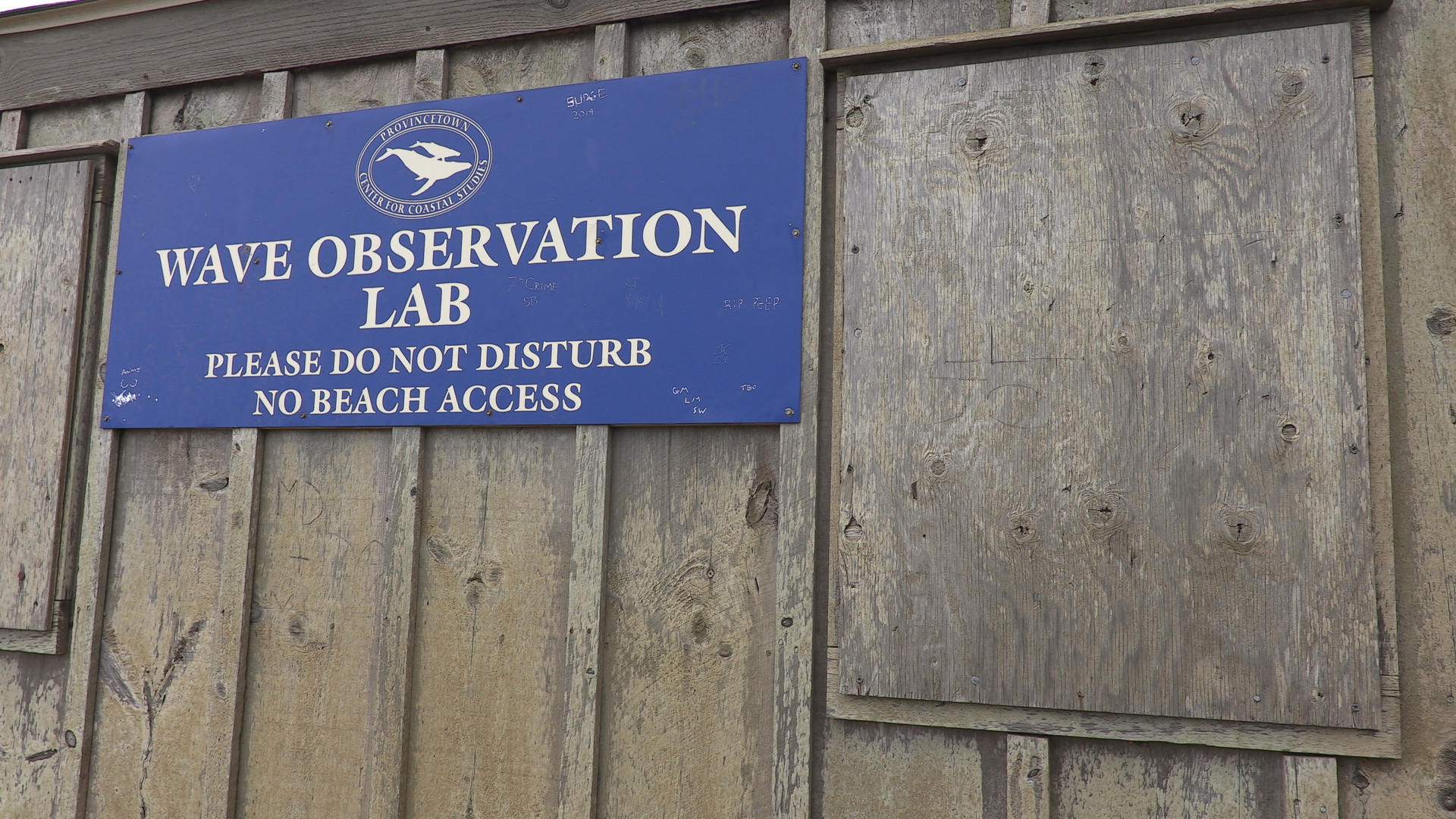 A sign on a wooden shed that states WAVE OBSERVATION LAB.