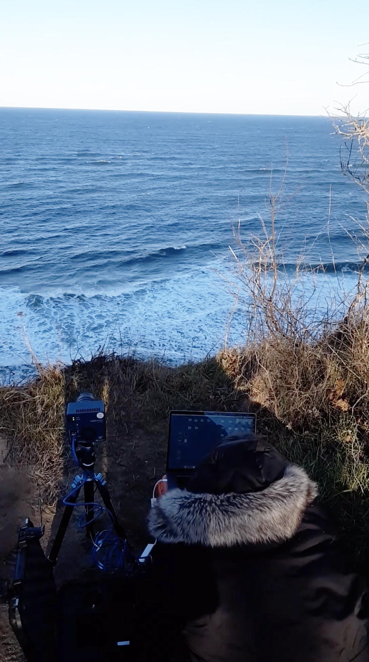 Person in heavy coat works with an Edgertronic Camera and laptop high above the sea.