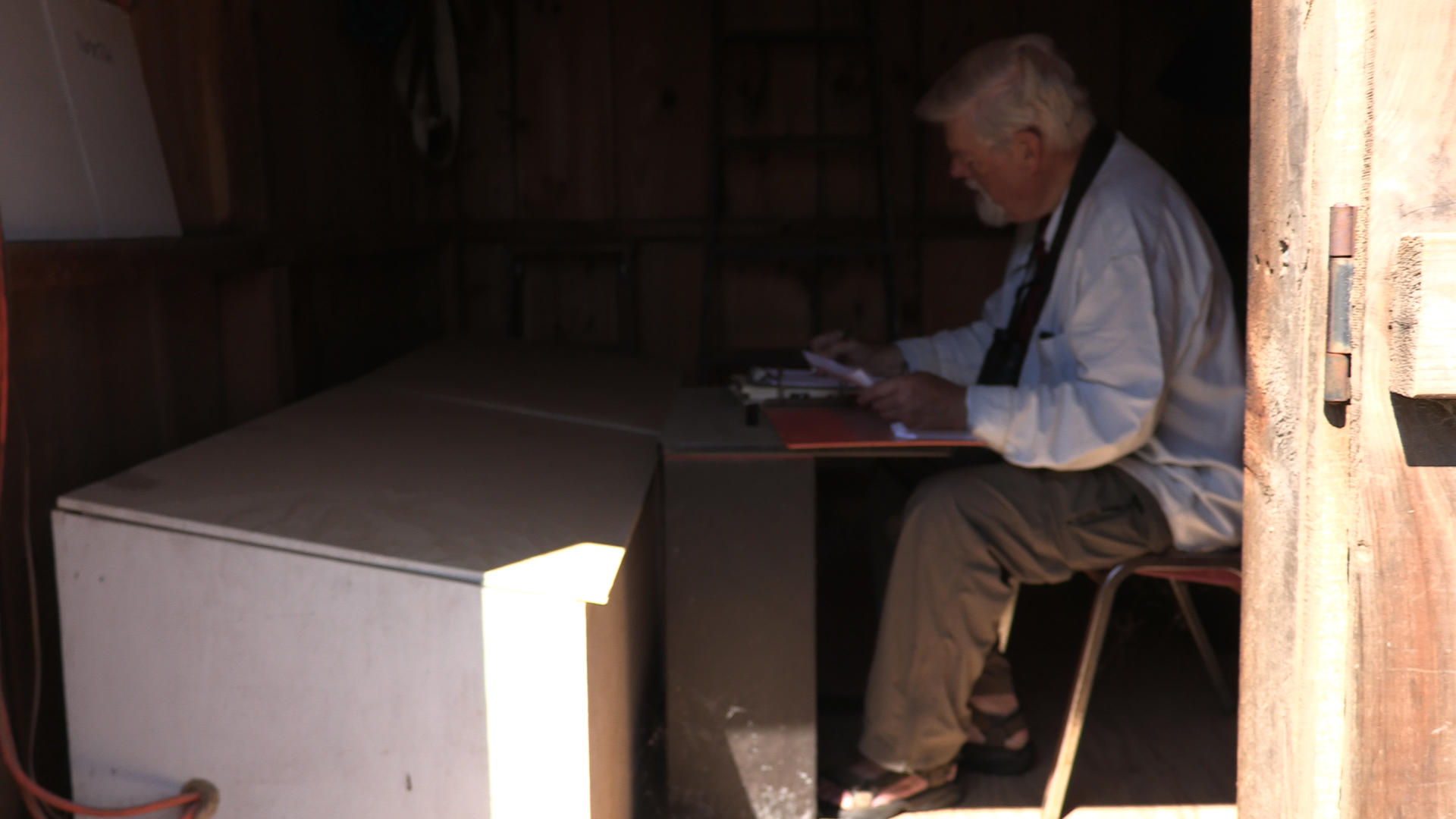 Man sits at a table in a wooden shed in Cape Cod MA recording the wave information.