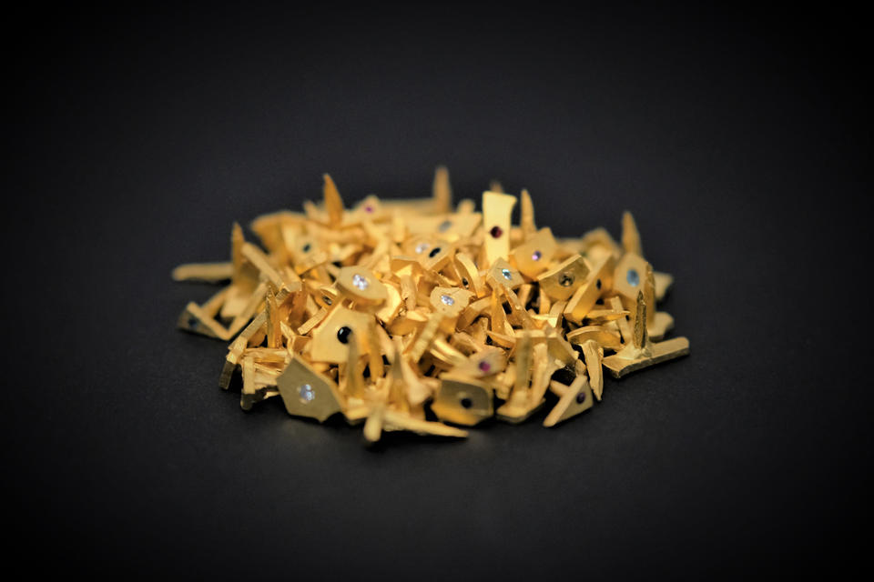 Photograph of a pile of small gold nails with diamonds