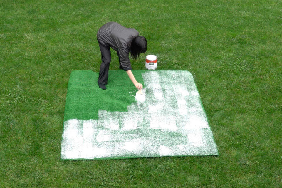 Photograph of a woman on grass painting astro turf with white house paint